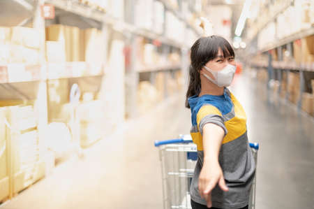 The asian girl wearing surgical mask pushing the trolley cart shopping the decorate funiture for interior inside the house in the big warehouse store.