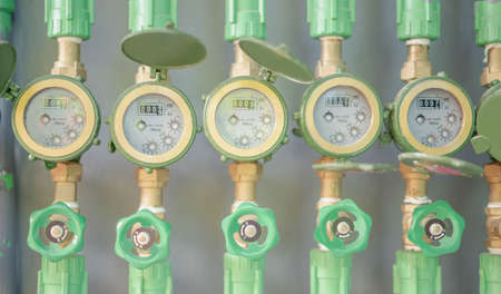 Row of industrial pipelines and valves with green wheels on  grey wall for check the standard water level located at the dormitory for check the price of the water. closeup view.