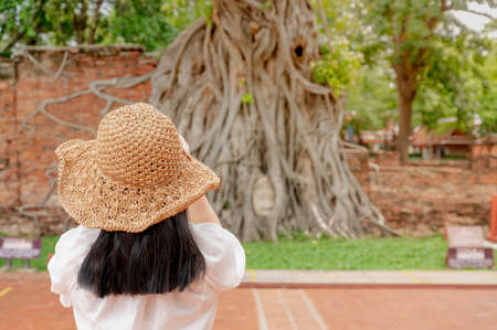 The back view of woman wearing hat for protect the sun travel at the ancient city Ayuttaya province old city of Thailand.