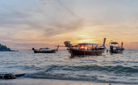Thai fishing boat used as a vehicle for finding fish in the sea or for the traveler go to other island in the sea or ocean in the morning time. The sky is clear.