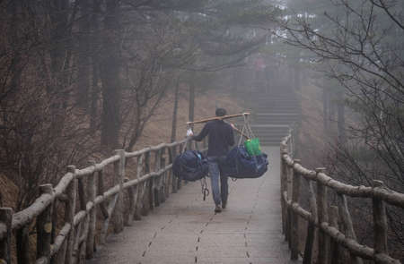 The worker man carring foods or backpacker for the tourism that hiking to the peak and its extra fee for worker at Huangshan montain, Anhui province, China.