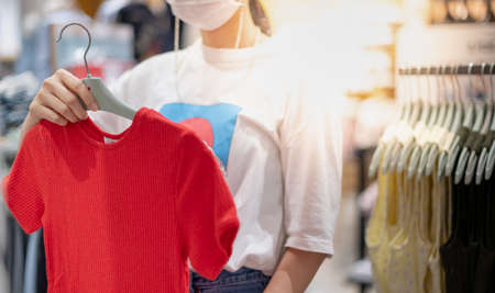 Asian woman wearing surgical mask and choosing the red t-shirt clothes and looking to mirror in mall or clothing store. Beauty and Fashion and choice concept.a Stock fotó
