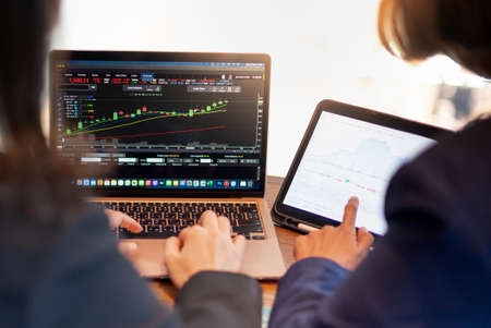 Two business investor trading or stock brokers having a planning and analyzing with display screen and pointing on the data presented and deal on a stock exchange.