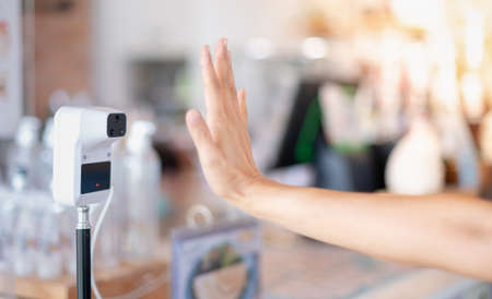Female hand use digital temperature machine for measuring body temperature that placing a hand over the sensor in a cafe for mandatory checks of customers before come into the shop.