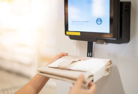 Female hand holding goods scanning barcode on information machine for check the price and information of the goods. Technology scanning barcode concept.