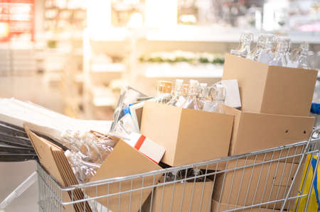 Many carton and glass bottle in the stainless trolley at Supermarket aisle preparing for arrange put on the shelves for customer to buy for decorate in house for interior concept.