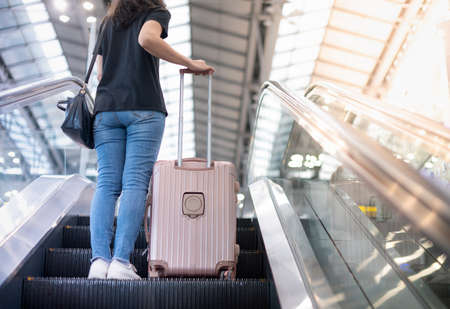 Asian girl wearing casual t-shirt and carrying the suitcase luggage on the escalator at the airport, During the Covid19 epidemic pandemic for business trip.