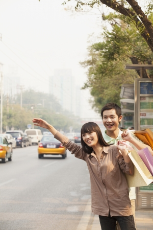 taxicab: Young couple with shopping bags hailing a taxicab in Beijing