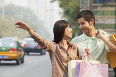 hailing: Young couple looking at each other with shopping bags hailing a taxicab in Beijing