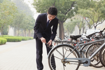 Young businessman locking up his bicycle on a city street in Beijing photo