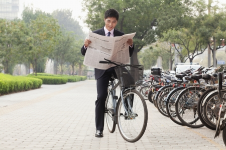 Young businessman sitting on a bicycle and reading the newspaper photo