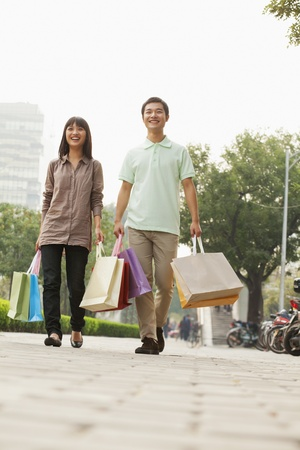 Young couple walking with shopping bags in hands, Beijing, China  photo