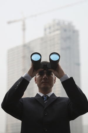 Young Businessman Using Binoculars and Looking into the Distance, Low Angle View photo