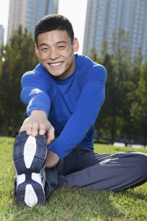 touching toes: Young Athletic Man Stretching in Beijing Park- Vertical