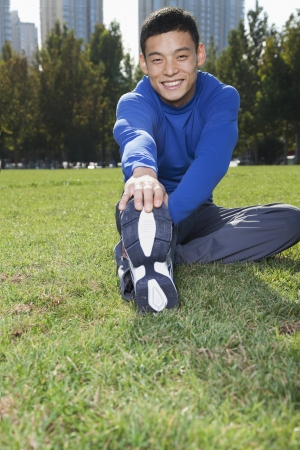 touching toes: Young Athletic Man Stretching in Beijing Park