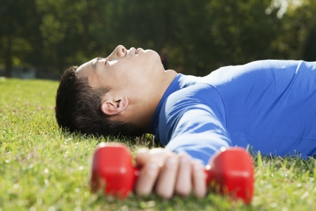 man lying down: Young Athletic Man Lying Down in Park with Dumbbells