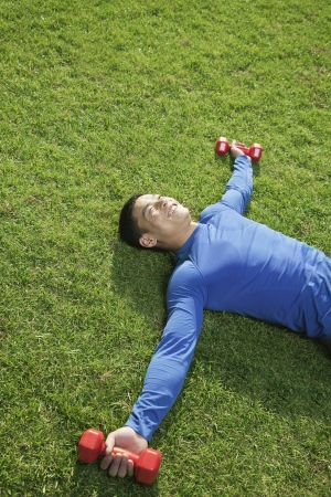man lying down: Young Athletic Man Lying Down in Park with Dumbbells in Grass
