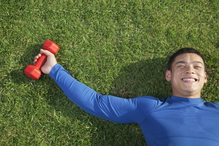 man lying down: Young Athletic Man Lying Down in Grass with Dumbbells, Directly Above View