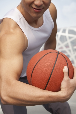 bicep: Young man showing bicep and holding basketball