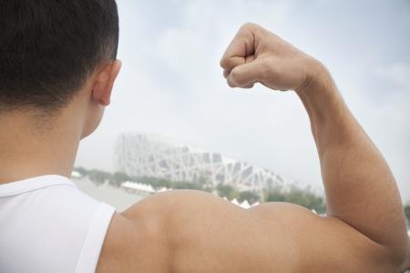 tilt view: Rear view of young man flexing his bicep, tilt