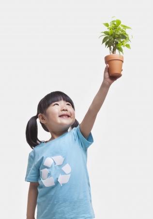 ni�os reciclando: Ni�a que sostiene la planta en maceta sobre su cabeza, tiro del estudio Foto de archivo