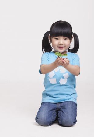 Little girl holding a seedling, studio shot Stock Photo - 21156197
