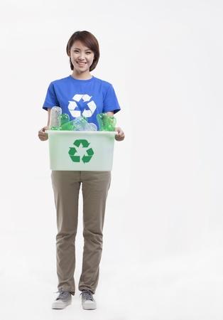 recycling bin: Portrait of young woman holding recycling bin, studio shot