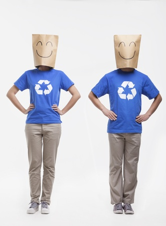 Two young people with smiley face paper bags over their head