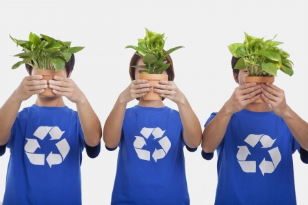 obscuring: Three people holding plants, obscuring faces, studio shot