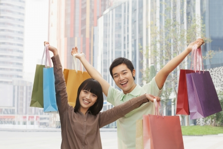 Portrait of young couple posing with shopping bags in hands, Beijing, China  photo