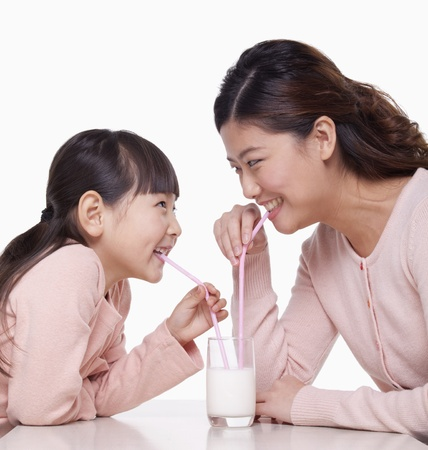 Mother and daughter sharing a glass of milk, studio shot photo