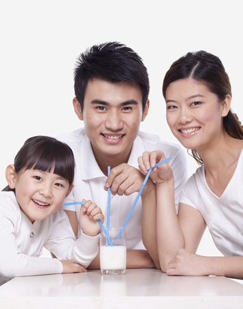 Family sharing a glass of milk, studio shot photo