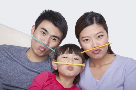 making a face: Portrait of family making a face with drinking straws