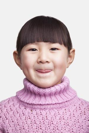 sticking tongue: Retrato de la ni�a sonriente que pega la lengua hacia fuera, foto de estudio Foto de archivo