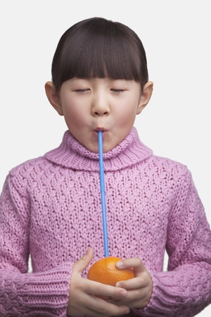 Portrait of young girl drinking an orange with a straw, studio shot Imagens
