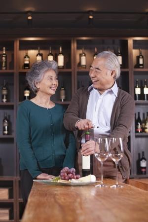 Senior Couple Opening Wine Bottle photo