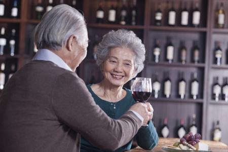 Senior Couple Toasting and Enjoying Themselves Drinking Wine, Focus on Female