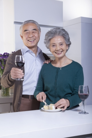 Senior Couple in Kitchen Drinking Wine and Cheese