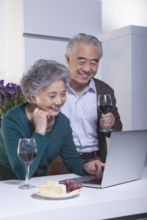 chinese people: Mature Couple Looking at Laptop in the Kitchen, Drinking Wine  Stock Photo