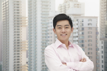 button down shirt: Portrait of young businessman in button down shirt with arms crossed, skyscraper in background