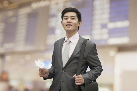 Young businessman holding ticket at the airport, Beijing, China