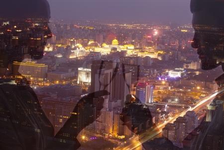 brindisi spumante: Doppia esposizione di coppia tostatura con champagne flutes sul paesaggio urbano di notte