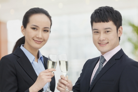 champagne flutes: Young business man and woman toasting with champagne flutes