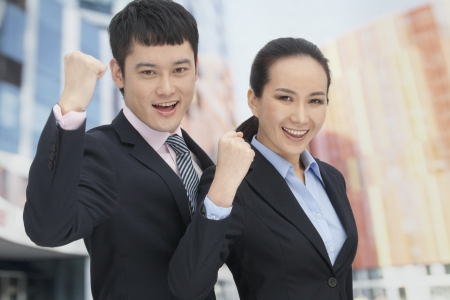 Young business man and woman cheering Imagens