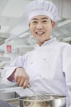 Chef whisking in bowl, portrait photo