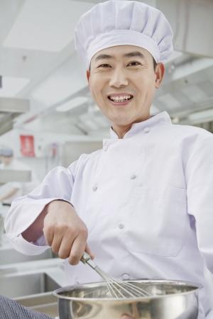 Chef whisking in bowl, portrait photo