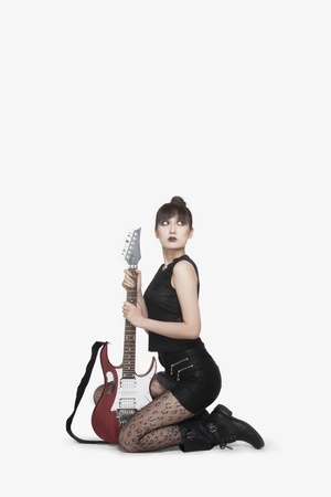 counterculture: Punk Rocker Kneeling with Guitar Stock Photo