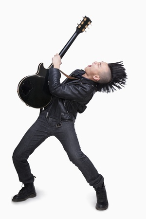 spiky hair: Young man with punk Mohawk playing guitar