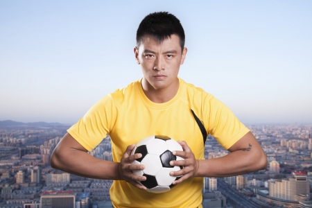 Footballer holding ball to chest, cityscape background Imagens