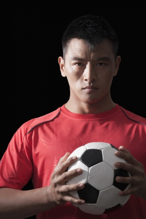 Footballer holding ball to chest, black background